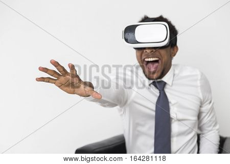 Portrait of an African American man in a white shirt who is sitting in a leather armchair and wearing vr glasses. Concept of escaping the reality to overcome difficulties.