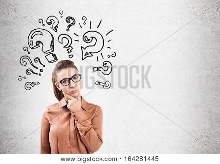 Thinking woman in glasses with her fingers on the chin is standing near a concrete wall with question marks. Mock up