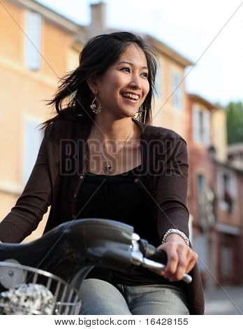 Young woman on a bicykle, smiling