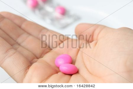 Taking pills/taking painkillers - hand holding two pills/tablets isolated on white with some more pills in the background