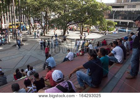 Medellin,  Colombia - December 13, 2016: Peoples are sitting on stairs of Berrio Park and listen a man who make propaganda of catholism