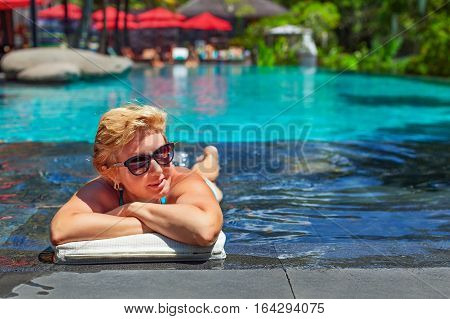 Successful retirement recreation summer vacation concept. Retired mature person enjoying beautiful sunny day in swimming pool at beach club. Happy senior woman rest lying in water at black poolside.