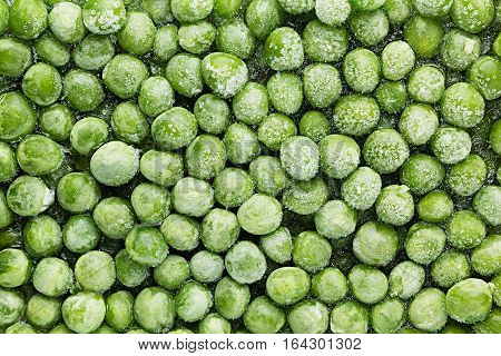 Fresh frozen green peas with hoarfrost closeup as background. Healthy vitamin food.