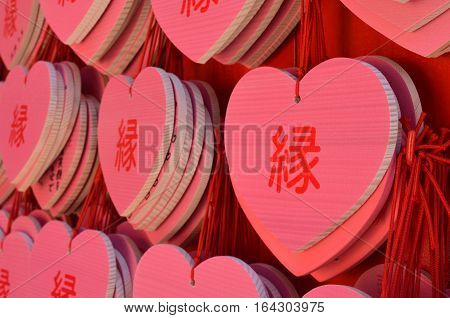 Wish plaques, called ema, displayed by people in hopes of falling in love at a shrine in Japan. The character says