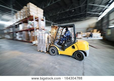 Moscow, Russia - December 13, 2016: Warehouse transport and logistics company. Forklift transporting loads inside the industrial warehouse.