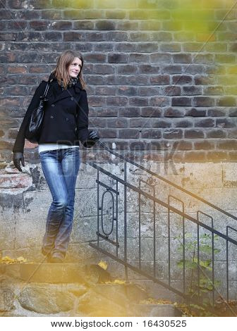 pretty & elegant young woman standing by a small staircase outdoors in a park on a lovely fall day