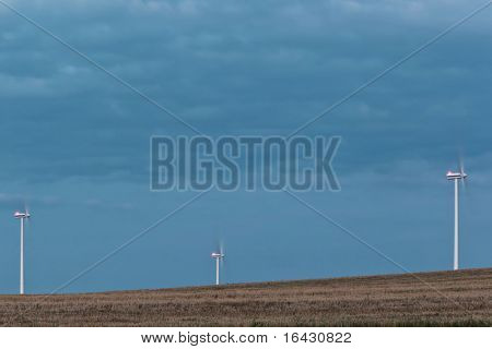 landscape with three wind enery harvesting wind mills