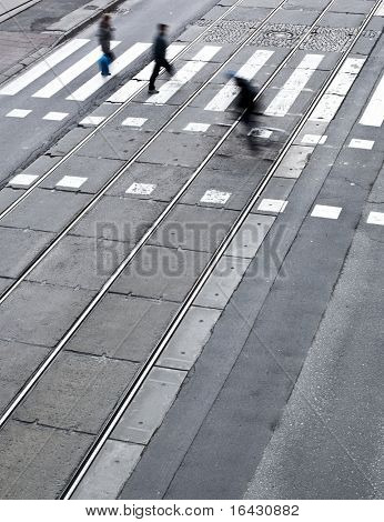 urban traffic concept - city street with a crossing, rail, motion blurred cyclist and pedestrians (color toned image)