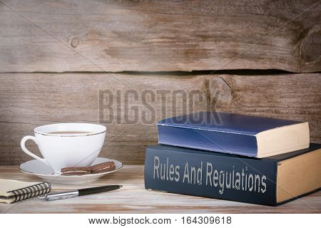 Rules And Regulations. Stack of books on wooden desk.