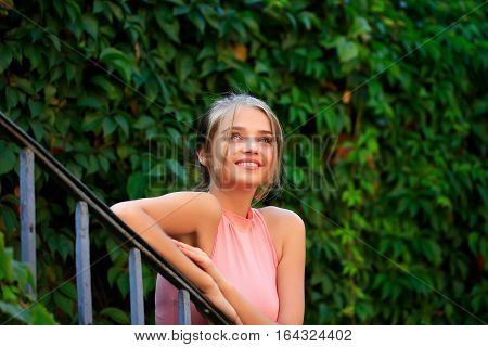 Pretty young woman or girl with tied in bun blonde hair in pink shirt with cute face lean on stair with green ivy wall on background