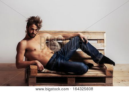 Young handsome man or muscular macho with sexy torso sits on wooden pallet sofa on grey background in jeans