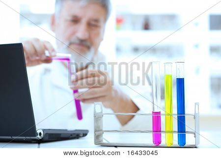 senior male researcher carrying out scientific research in a lab (color toned image)