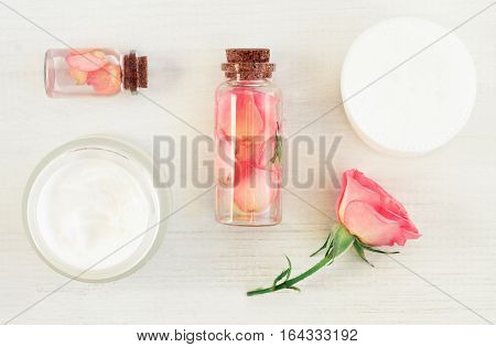 Set of aromatic botanical cosmetic products on white wooden table. Glass bottles with extract, tonic infused with flower petals, fresh pink rose, cotton pads. Soft light and focus.