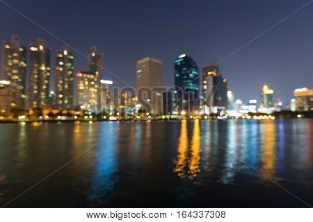 Night blurred lights office building with water reflection abstract background