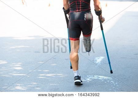 Triathlon Cup of Ukraine and Cup of Bila Tserkva. July 24 2016 in Bila Tserkva Ukraine. Paralympic disabled man athlete on crutch