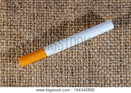 Cigarette Left On The Brown Crumled Background, Close Up With Copy Space