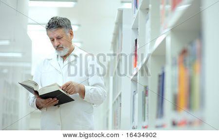 Renommierte Wissenschaftler/Arzt/Professor in einer Bibliothek Forschung Zentrum/Krankenhaus - Surfen ein Buch