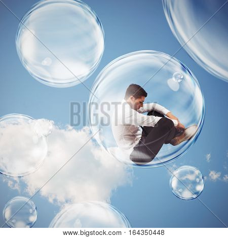 Sad businessman flies in a bubble. isolate themselves inside a bubble detachment from the outside world concept