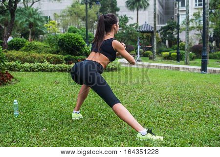 Back view of fit girl doing side lunge exercises outdoors.