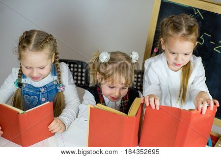 Three Young Schoolgirls With Red Textbooks