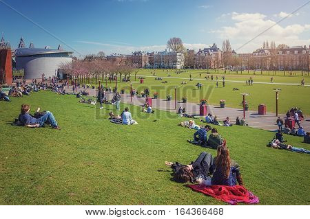 Amsterdam, Netherlands, April 10, 2015: People chilling in the sun on The Museumplein in Amsterdam at the background The Van Gogh Museum