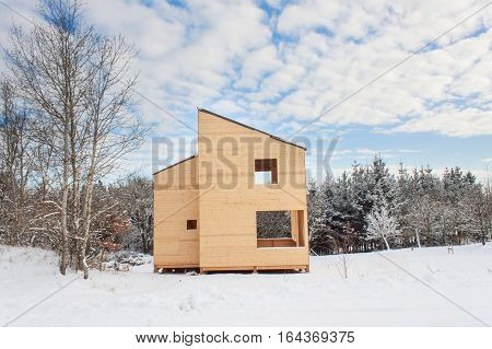 Snowy site ecological house. The wooden house in the woods.
