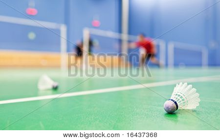 badminton - indoor badminton courts with players; shallow DOF, sharp focus on the shuttlecock in the foreground (color toned image)