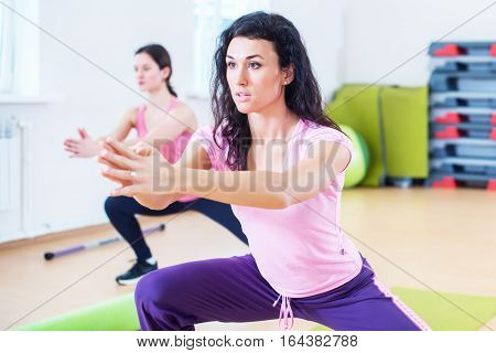 Fit women doing side lunges, exercises for legs, hips and buttocks