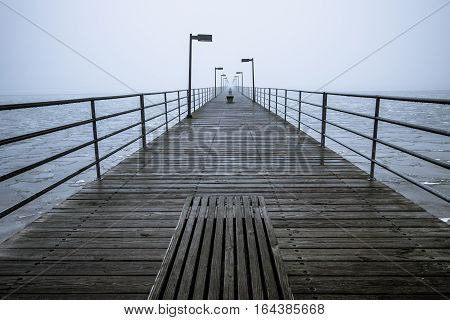 Foggy Pier On The Great Lakes Coast. Long wooden pier diminishing into the foggy Great Lakes Horizon. Harbor Beach, Michigan.