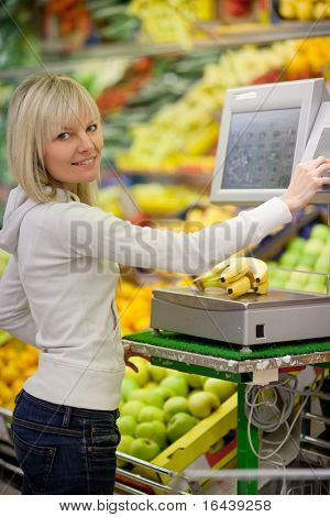Beautiful young blonde woman shopping for fruits and vegetables in produce department of a grocery store/supermarket (shallow DOF; color toned image)
