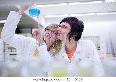 two female researchers carrying out research in a chemistry lab (color toned image; shallow DOF)