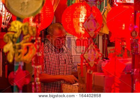 January 2 2017. A shopkeeper stands in his shop with red Chinese lanterns paper hangings and golden decorations on sale for the Chinese New Year. Chinatown Singapore.