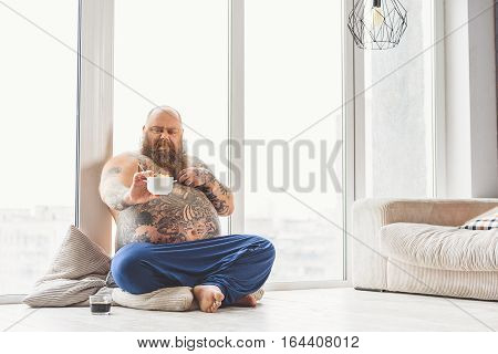 I hate healthy food. Mature thick guy is holding bowl of cornflakes and looking at it with disgust. He is sitting near window at home