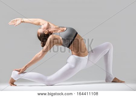 Young attractive woman practicing yoga, standing in Horse rider exercise, anjaneyasana pose, working out wearing sportswear, white pants, gray top, indoor full length, grey studio background