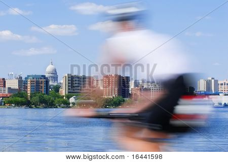 Motion Blur of a person riding a bicycle past the capitol city of Wisconsin in Madison
