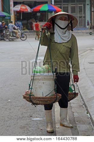 Ha Long city Vietnam - June 3 2015: woman is carrying a load in shoulder-yoke outdoor in Ha Long city Vietnam