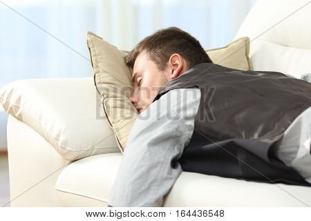Tired businessman sleeping lying on a couch after work at home