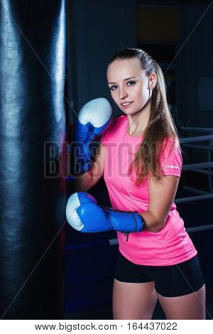 Attractive Young Woman With Blue Boxing Gloves In Sport Gym. Beautiful Female Boxer With Punching Ba