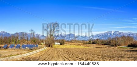 Agricultural winter panorama. Small solar power station. Italian Alps in the background