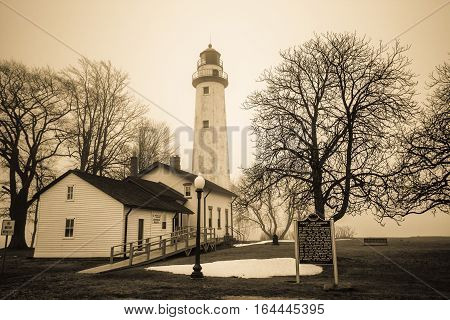 Haunted Great Lakes Michigan Lighthouse.  The reportedly haunted Pt. Aux Barques Lighthouse on the remote shores of Lake Huron surrounded by bare trees in vertical orientation. Port Hope, Michigan.