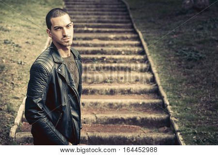 Model handsome man near steps. A handsome young man model outdoors. Near the steps in a park. He wears a leather jacket. Short hair almost shaved. Expression of anxiety or doubt.