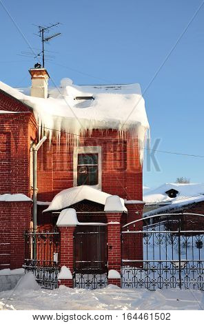Icicles on the roof of the cottage. Winter.