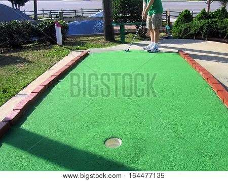 playing putt putt golf on a putting green