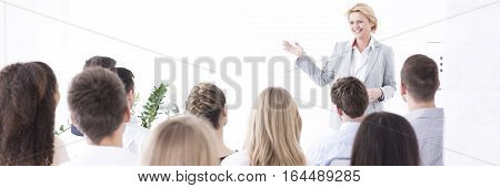 Presentation given by a middle-aged businesswoman to a group of people
