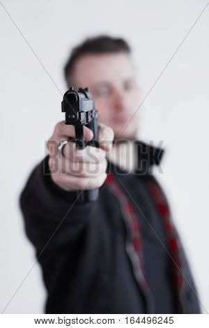 Closeup of focused young man standing and aiming with gun. Bomber