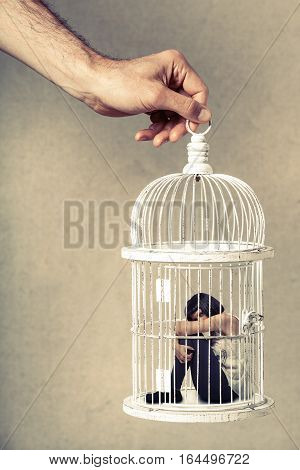 Violence against women. Woman in cage. Deprivation of liberty. Young woman locked in a cage. Young girl crouched position. A male hand holding the cage from above. Concept of deprivation of liberty and freedom of autonomy. Violence against woman and girls