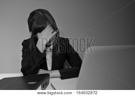 Stressed or headache businesswoman at office desk - black and white failure business concept