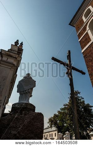 Nesvizh Belarus - September 12 2016: The cross with the crucifixion of Jesus Christ sculpture of Saint Yan Nepomuk and the church bell tower in the territory of the The Corpus Christi Church in Nesvizh Belarus