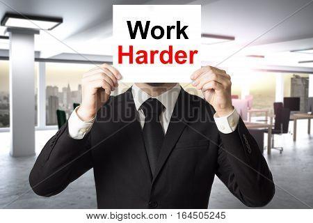 businessman in modern office hiding face behind sign work harder