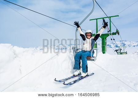 Happy female skier riding a lift. Skiing in sunny weather.